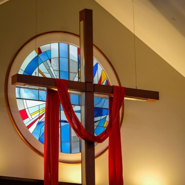 A cross hanging in the church in front of a stained glass window